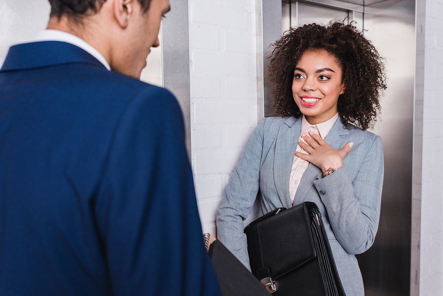 African american businesswoman with briefcase talking to man by elevator