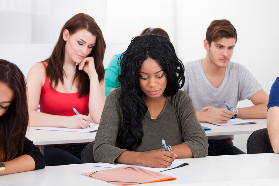 Group of multiethnic college students writing at desk in classroom