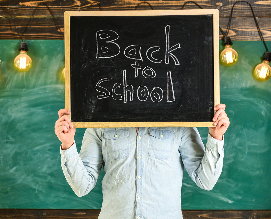 Start of school year concept. Teacher faceless holds blackboard with title back to school. Man welcomes students, chalkboard on background. Teacher holds chalkboard in front of face.