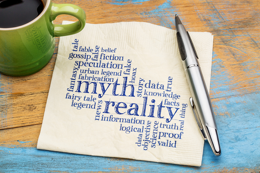 myth versus reality word cloud - handwriting on a napkin with cup of coffee