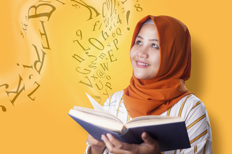 Portrait of Asian Muslim woman smiling when reading book, magical book with letters flying from it