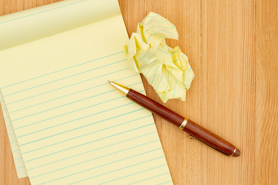 Yellow legal notepad paper with crumpled paper and pen on wood desk with copy space for your business or writing message or mockup