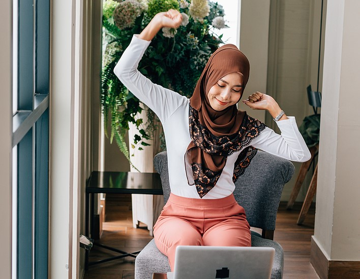 Happy Asian woman in hijab raising arms and stretching body while working with laptop in cozy cafe