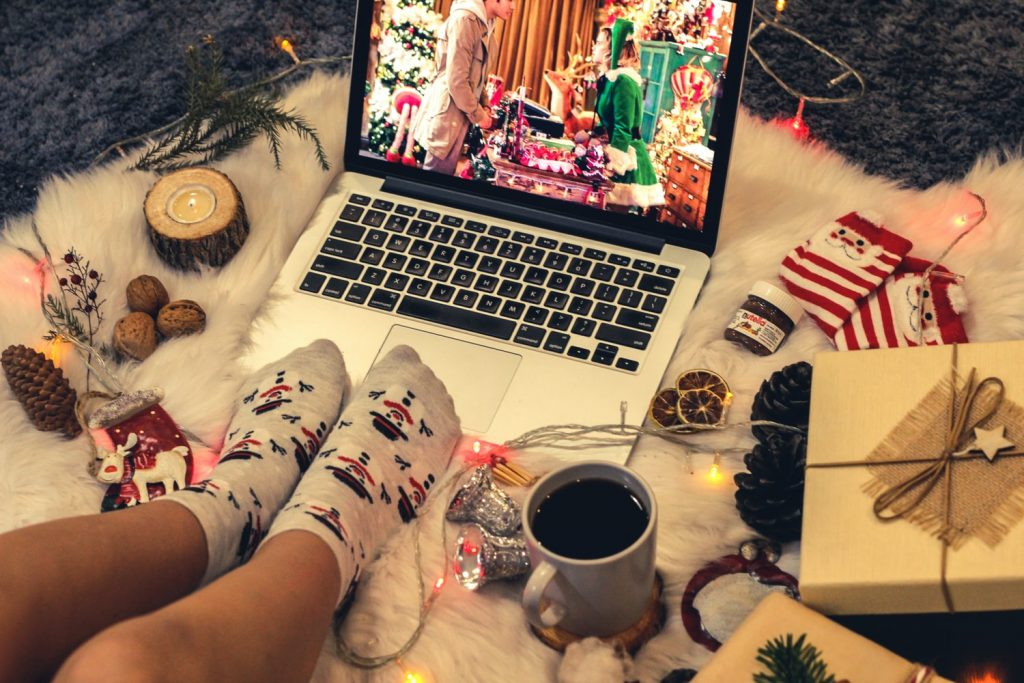 A person using a laptop while surrounded by holiday gifts, decorations, and treats.